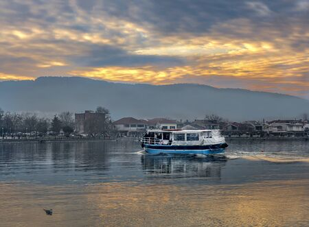 Sunset on Ioannina city. Small wooden boat floating the calm waters on lake Pamvotis and transfer passengers to a  very small island inside the lake. Greece.
