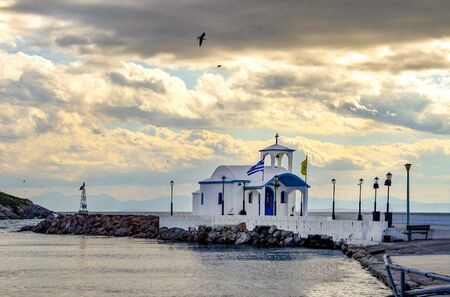 Small chapel with white roofs on cliff over sea and small bay under a dramatic sky on a Greek island