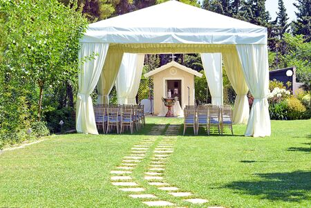 white wedding or entertainment tent with a very small chapel, and a baptism bowl, in a grass field on a sunny summers day