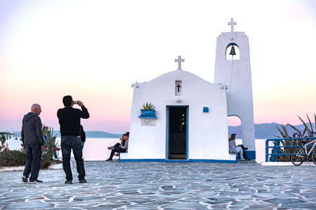 Rafina,Greece -03252017: People photo shooting, resting and enjoy the view. White small orthodox chapel dedicated to St Nikolaos. Redactioneel