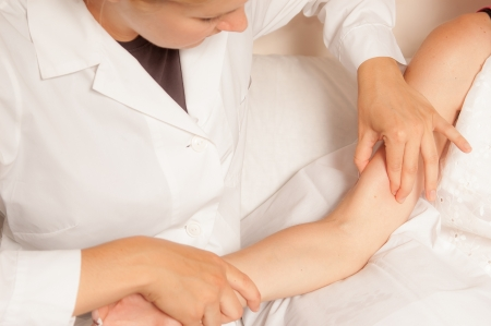 female elbow: A physio gives myotherapy using trigger points on athlete woman Stock Photo