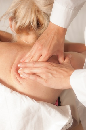 trigger: A physio gives myotherapy using trigger points on athlete woman Stock Photo