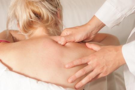 masaje deportivo: Un fisioterapeuta le da mioterapia con los puntos de activaci�n en la mujer deportista