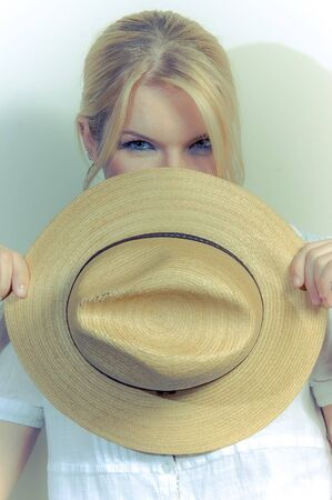 A beautiful girl with a straw hat against a white wall
