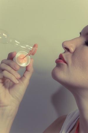 A beautiful blonde girl making soap bubbles Stock Photo