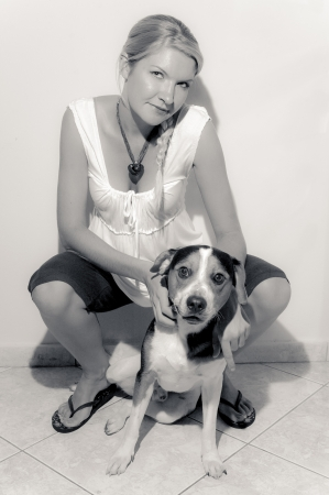 A girl with her dog against a white wall