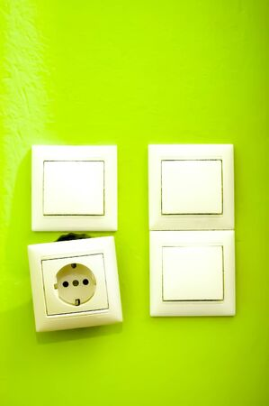Electric switches and broken socket on a green wall