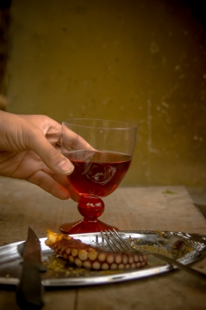 A hand holding a glass with red wine and a plate with barbecued octopus piece photo