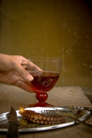 A hand holding a glass with red wine and a plate with barbecued octopus piece