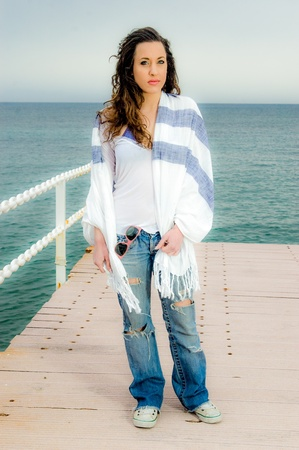 Beautiful teenager girl fashion shot on a peer, next to the sea
