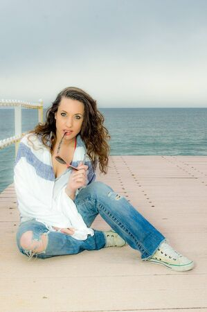 Beautiful teenager girl fashion portrait on a peer, next to the sea