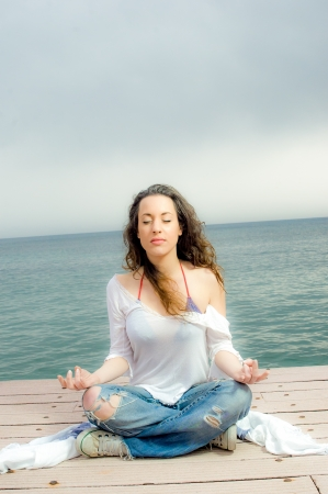 Beautiful girl in meditation on a peer next to the sea photo