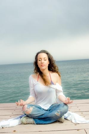 peer to peer: Chica hermosa en la meditaci�n de un compa�ero al lado del mar