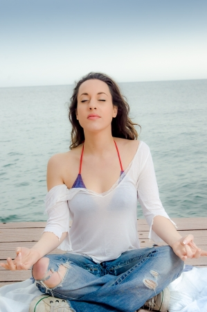 Beautiful girl in meditation on a peer next to the sea