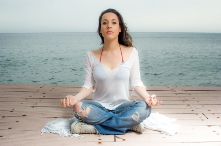 yoga girl: Beautiful girl in meditation on a peer next to the sea