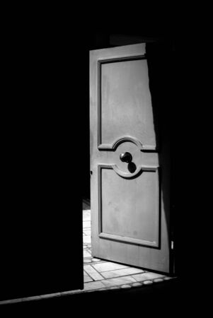 Open metallic door in black and white, Step into the light concept