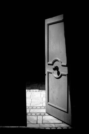 portone: Porta metallica aperta in bianco e nero, passo nel concetto di luce Archivio Fotografico