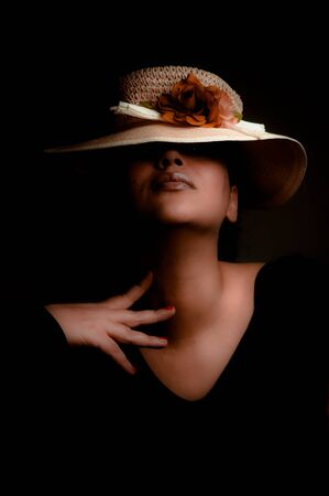 Low key portrait of a beautiful multiracial girl wearing a hat with flowers