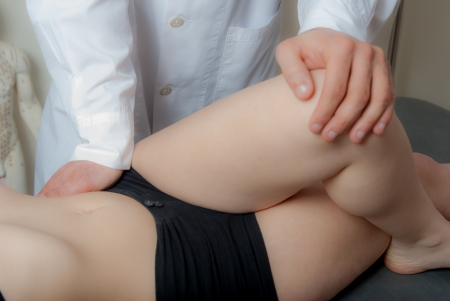 on hands and knees: Manual, physio and kinesio therapy techniques performed by a male physiotherapist on a training plastic spine and a female patient