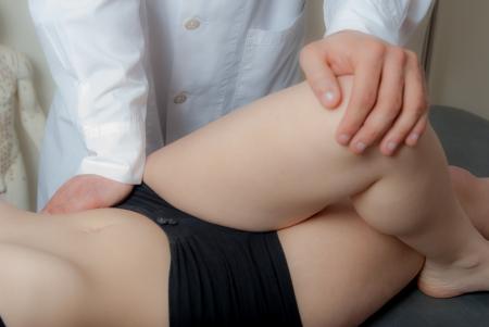 sports massage: T�cnicas de terapia manual, fisioterapia y Kinesio realizadas por un fisioterapeuta macho en una columna de pl�stico formaci�n y una paciente Foto de archivo