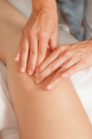 on hands and knees: A physio gives myotherapy using trigger points on athlete woman Stock Photo