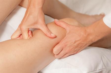 massage jambe: Un physio donne myotherapy utilisant des points de d�clenchement sur la femme athl�te