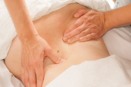 male massage: A physio gives myotherapy using trigger points on athlete woman Stock Photo