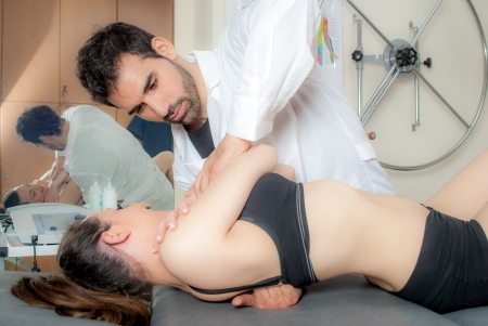 alternative: Manual, physio and kinesio therapy techniques performed by a male physiotherapist on a training plastic spine and a female patient