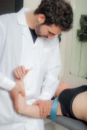Manual, physio and kinesio therapy techniques performed by a male physiotherapist on a training plastic spine and a female patient