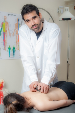 Manual, physio and kinesio therapy techniques performed by a male physiotherapist on a training plastic spine and a female patient photo