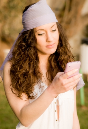 A beautiful girl at the park using a mobile phone