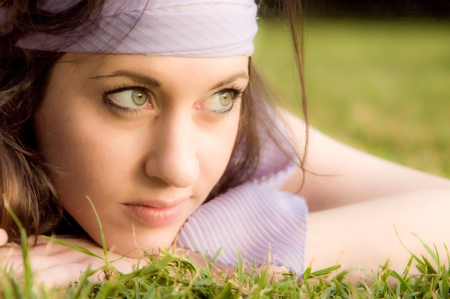 Portrait of a beautiful girl, lying at the grass at the park Stock Photo