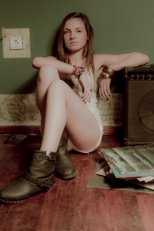 glam rock: A beautifull teenage girl and a sound amplifier on an old wooden floor with fashion accessories