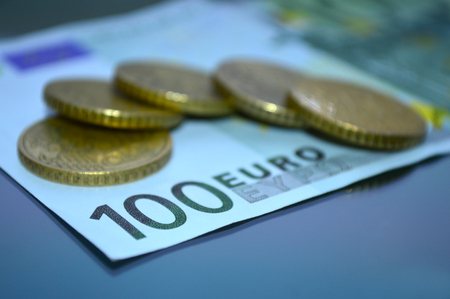 A denomination of 100 euros and coins spread on it Archivio Fotografico