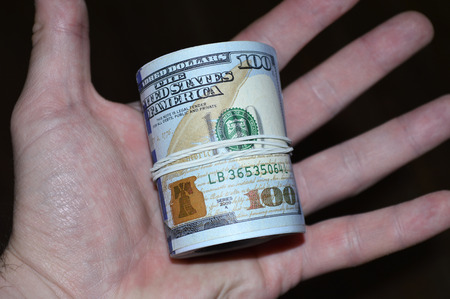 A twisted bundle of 100 dollar bills in a hand on a black background
