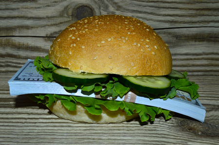 Hamburger with a bunch of dollars on a wooden table background 写真素材