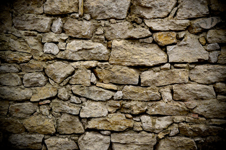 Old rough stone wall made of sandstone