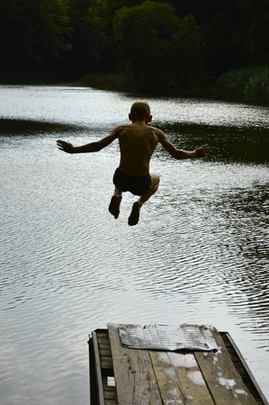 The boy jumps from the dock to the river