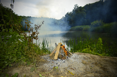 A bonfire in a forest near a beautiful lake