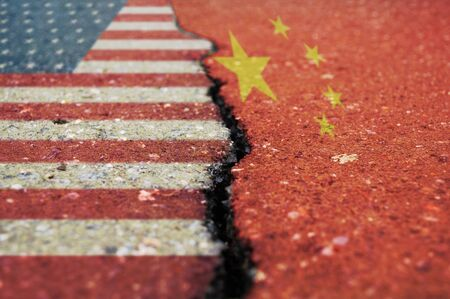 Flags of America and China on asphalt are separated by a crack. 스톡 콘텐츠
