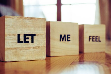 Wooden cubes with the words LET ME FEEL close up