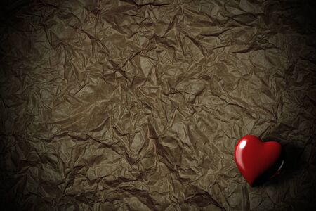 Red heart in a corner on crumpled paper