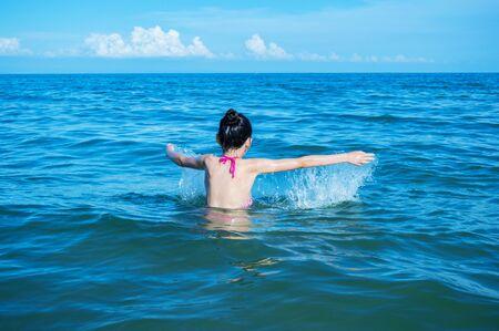 Teen girl splashing in the blue sea close up Stockfoto