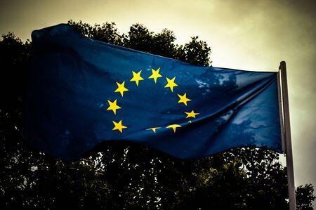 European Union flag on gray sky background close up