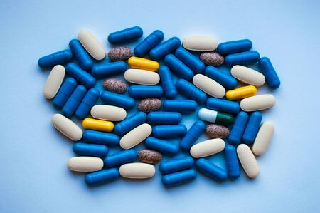 Capsules are scattered on a white surface close up. Medicine concept Stok Fotoğraf