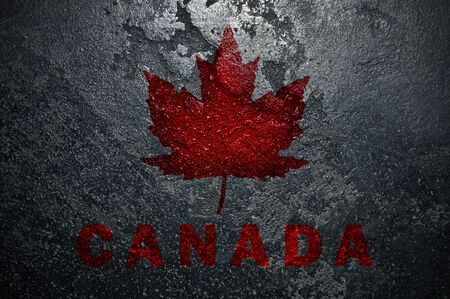 On a rough Black stone a maple leaf and the inscription Canada.