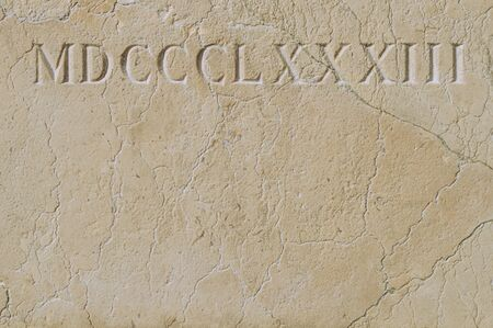 Old roman numerals engraved on a texture stone close up