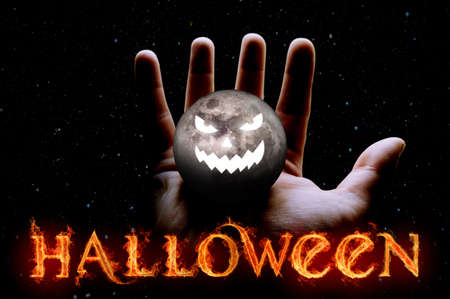 A hand holds the moon with a scary face on a black background close up. Halloween concept