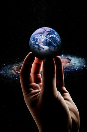 A man's hand holds the globe close up in detail. 免版税图像