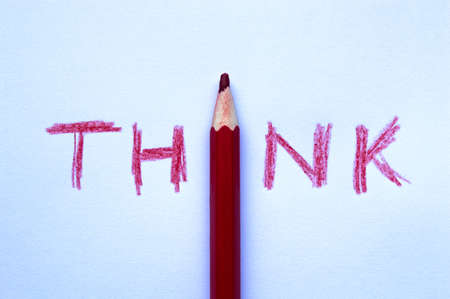 The word THINK is written in red pencil on a sheet close up 免版税图像